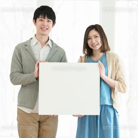メッセージボードを持ち微笑む夫婦の写真素材 [FYI01952755]