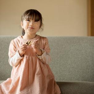 ソファーに座りクッキーを食べる女の子の写真素材 [FYI01952812]