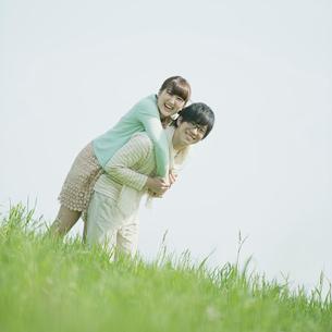 草原でじゃれあうカップルの写真素材 [FYI01952816]