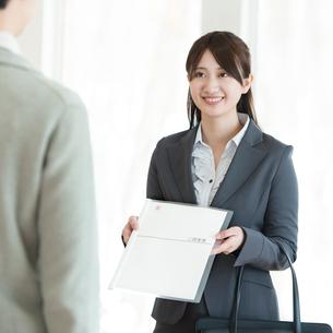 書類を持ち微笑むビジネスウーマンの写真素材 [FYI01952848]