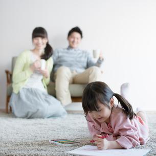お絵かきをする女の子と見守る両親の写真素材 [FYI01952855]