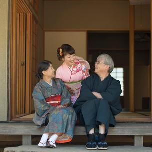 縁側に座り談笑をする家族の写真素材 [FYI01952908]