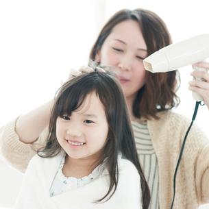 母親に髪を乾かしてもらう女の子の写真素材 [FYI01952941]
