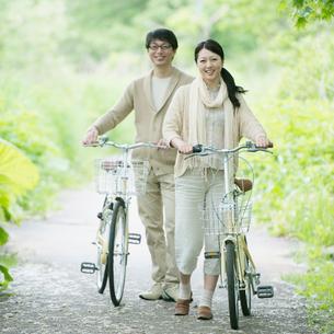 自転車を押すミドル夫婦の写真素材 [FYI01953038]