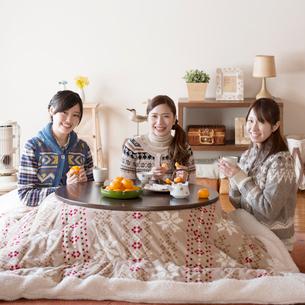 こたつで微笑む3人の女性の写真素材 [FYI01953067]
