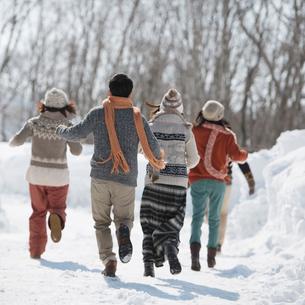 雪道を走る若者たちの後姿の写真素材 [FYI01953075]