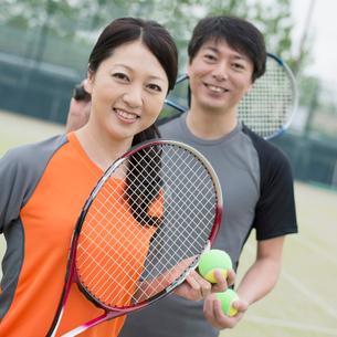 テニスラケットを持ち微笑むミドル夫婦の写真素材 [FYI01953157]
