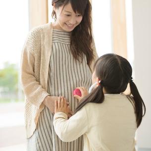 母親のお腹におもちゃの聴診器をあてる女の子の写真素材 [FYI01953173]