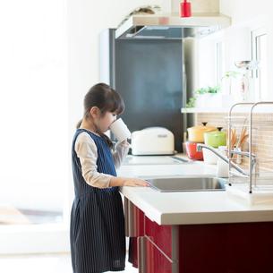 コップで水を飲む女の子の写真素材 [FYI01953180]
