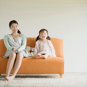 ソファーに座り微笑む親子の写真素材 [FYI01953202]