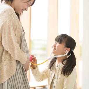 母親のお腹におもちゃの聴診器をあてる女の子の写真素材 [FYI01953227]
