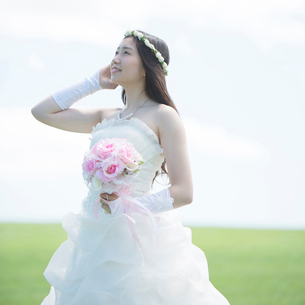 草原でブーケを持ち微笑む花嫁の写真素材 [FYI01953229]