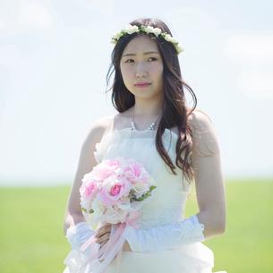 草原でブーケを持つ花嫁の写真素材 [FYI01953238]