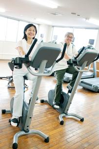 スポーツジムで運動するシニア夫婦の写真素材 [FYI01953247]