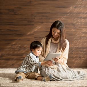 タブレットPCを見る親子の写真素材 [FYI01953278]