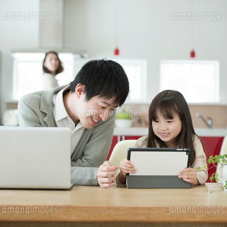 タブレットPCを操作する親子の写真素材 [FYI01953312]