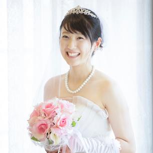 ブーケを持ち微笑む花嫁の写真素材 [FYI01953327]