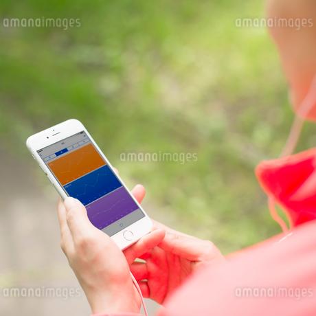 スマートフォンで活動量を見る女性の写真素材 [FYI01953335]