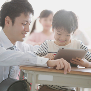 タブレットPCで勉強をする小学生と先生の写真素材 [FYI01953346]