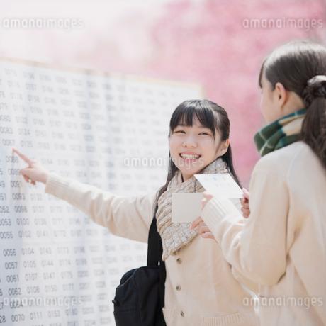 合格発表のボードを見て喜ぶ女子中学生の写真素材 [FYI01953349]