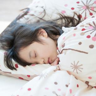 ベッドで眠る女の子の写真素材 [FYI01953373]