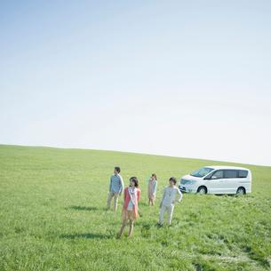 草原に佇む若者たちと車の写真素材 [FYI01953379]