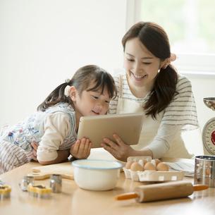 タブレットPCでレシピを調べる親子の写真素材 [FYI01953452]