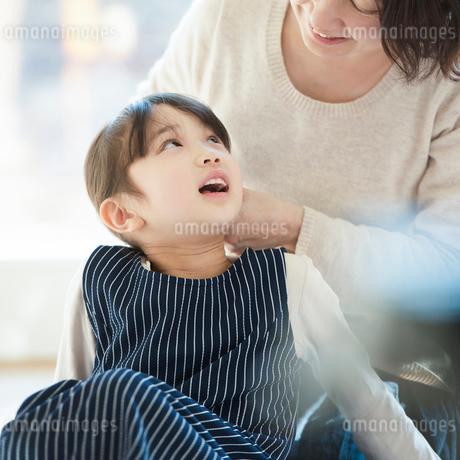 母親に髪を結んでもらう女の子の写真素材 [FYI01953461]