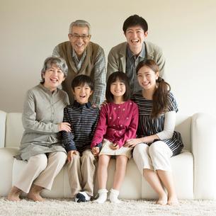 ソファーに座り微笑む3世代家族の写真素材 [FYI01953494]