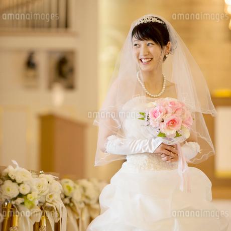 教会でブーケを持ち微笑む花嫁の写真素材 [FYI01953513]