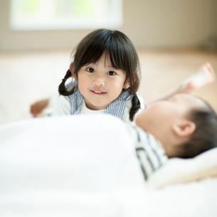 寝ている赤ちゃんに寄り添う女の子の写真素材 [FYI01953564]