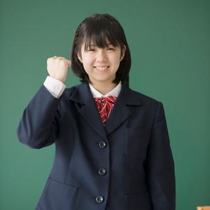 黒板の前でガッツポーズをする女子学生の写真素材 [FYI01953617]