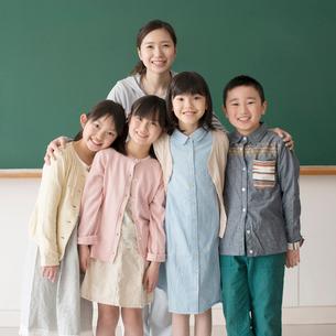 黒板の前で微笑む小学生と先生の写真素材 [FYI01953637]