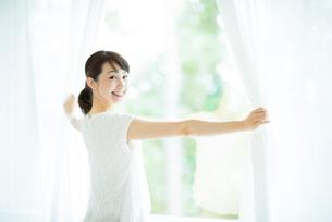 カーテンを開ける女性の写真素材 [FYI01953667]