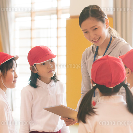 体育館で話をする小学生と先生の写真素材 [FYI01953683]