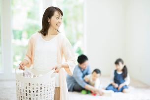 洗濯かごを持ち微笑む母親の写真素材 [FYI01953750]