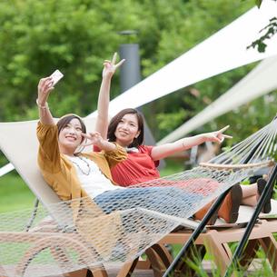 リクライニングチェアに座り自撮りをする2人の女性の写真素材 [FYI01953752]