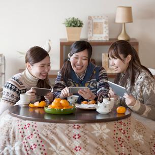 こたつでゲームをする3人の女性の写真素材 [FYI01953772]