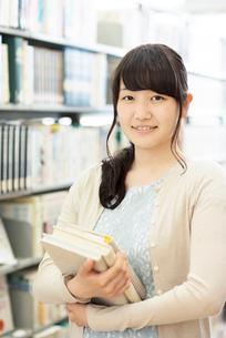 図書館で本を持ち微笑む女性の写真素材 [FYI01953786]