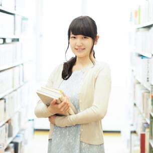 図書館で本を持ち微笑む女性の写真素材 [FYI01953807]
