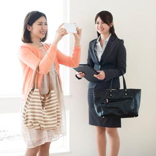 部屋の写真を撮る女性とビジネスウーマンの写真素材 [FYI01953810]