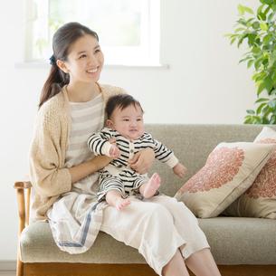 ソファーに座り微笑む母親と赤ちゃんの写真素材 [FYI01953818]