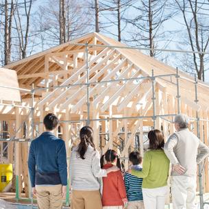 建設途中の家を眺める3世代家族の後姿の写真素材 [FYI01953861]