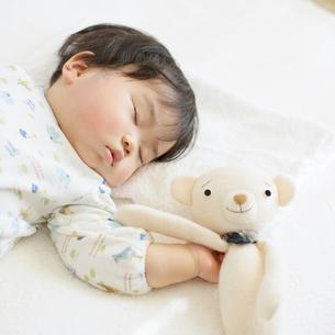 お昼寝をする赤ちゃんとクマのぬいぐるみの写真素材 [FYI01953879]