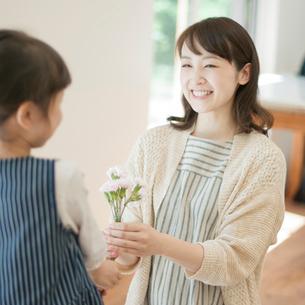 母親にカーネーションを渡す女の子の写真素材 [FYI01953880]