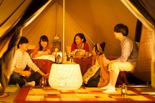 グランピングテントの中で談笑をする若者たちの写真素材 [FYI01953903]