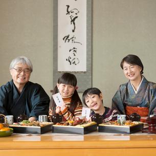 お年玉を持ち微笑む孫と祖父母の写真素材 [FYI01953947]