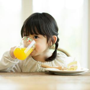 オレンジジュースを飲む女の子の写真素材 [FYI01953954]