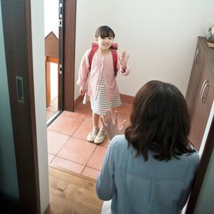 玄関で手を振る女の子の写真素材 [FYI01953992]