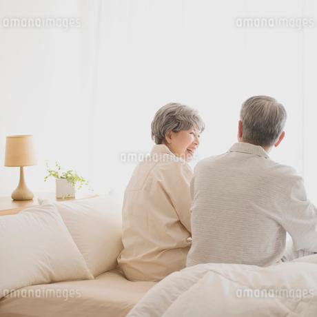 ベッドで談笑をするシニア夫婦の写真素材 [FYI01954032]